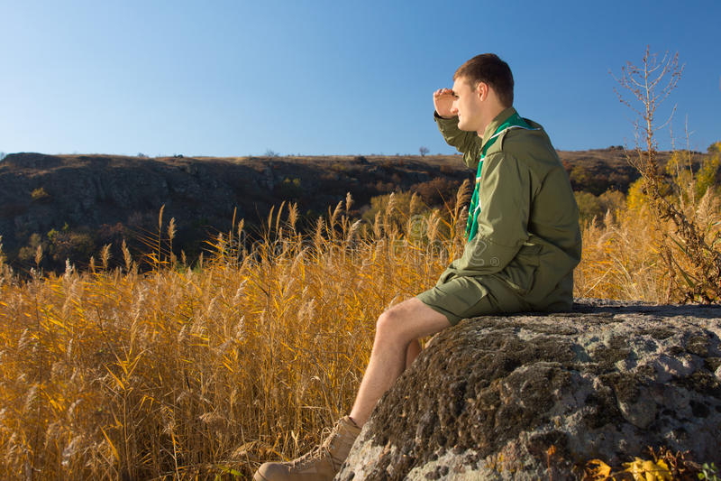 Giovane boy scout su roccia che guarda ampio campo fotografie stock libere da diritti