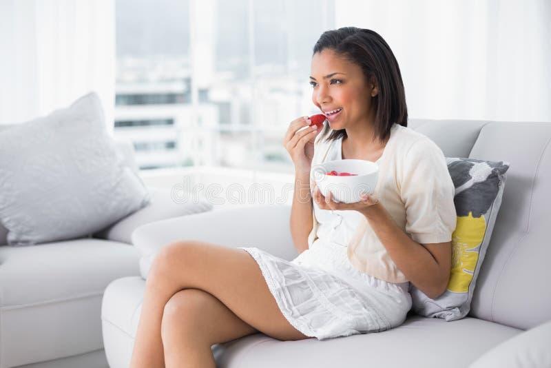 Giovane bruna adorabile in vestiti bianchi che mangia le fragole fotografie stock libere da diritti