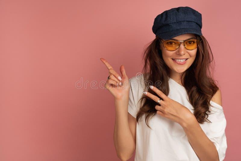 Giovane bruna con gli occhiali gialli ed i punti scuri del cappuccio a spazio sui precedenti con le sue dita immagini stock libere da diritti
