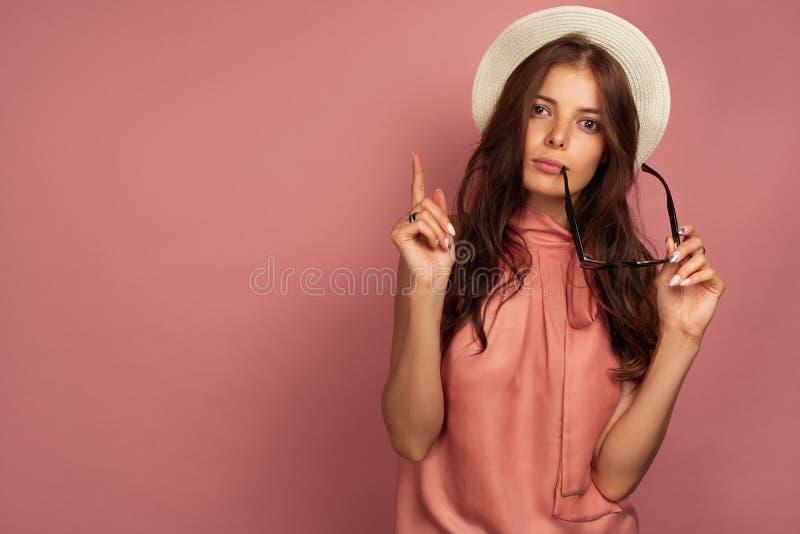 Giovane bruna con i punti del cappello di paglia sulla tenuta dei suoi occhiali da sole, fondo rosa fotografia stock