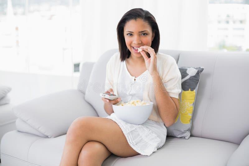 Giovane bruna sveglia in vestiti bianchi che mangia popcorn mentre guardando TV fotografia stock libera da diritti