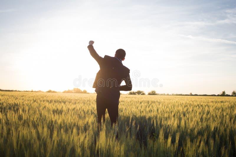 Giovane buisinesman felice dello stilysh con la mano rised durante l'aria aperta del sole immagine stock