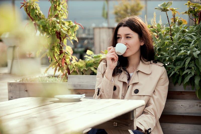 Giovane caffè grazioso della bevanda della donna in tazza all'aperto immagine stock libera da diritti