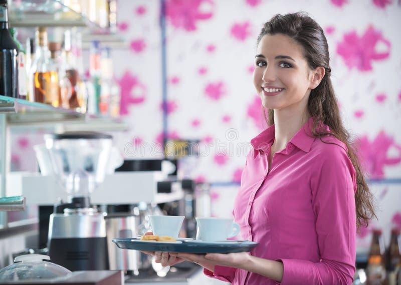 Giovane caffè sorridente del servizio della cameriera di bar alla barra immagini stock
