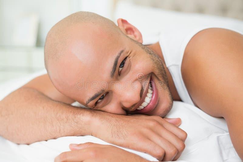 Giovane calvo casuale sorridente che si trova a letto fotografia stock libera da diritti