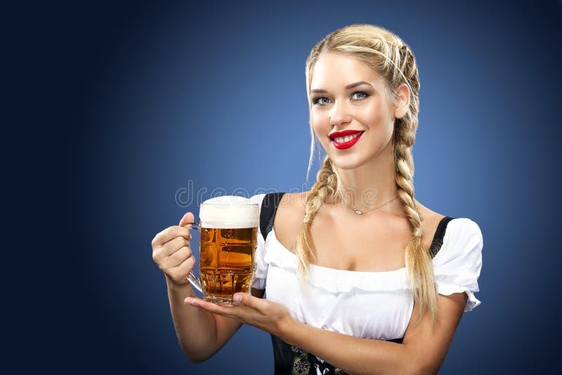 Giovane cameriera di bar sexy di Oktoberfest, portando un vestito bavarese tradizionale, grandi tazze di birra serventi su fondo  fotografia stock libera da diritti