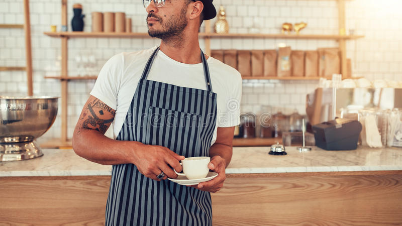 Giovane cameriere che sta al contatore del caffè fotografia stock libera da diritti