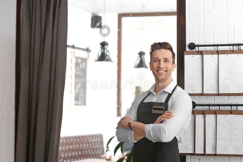 Giovane cameriere in grembiule fotografia stock