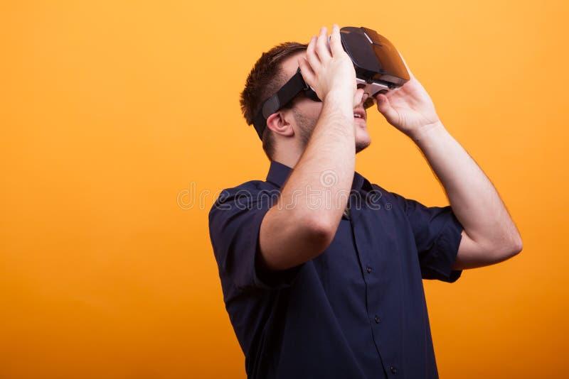 Giovane in camicia blu che indossa la cuffia avricolare di VR sopra fondo giallo fotografie stock libere da diritti