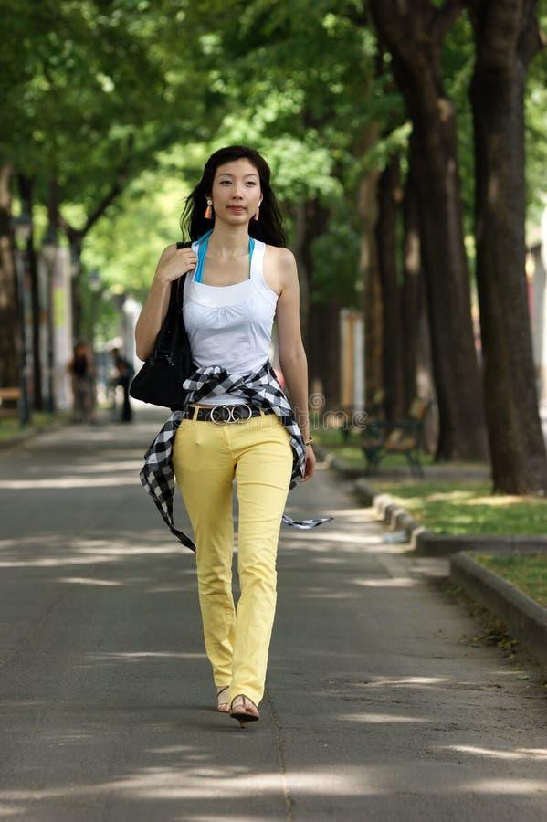 Giovane camminare asiatico della donna. fotografia stock