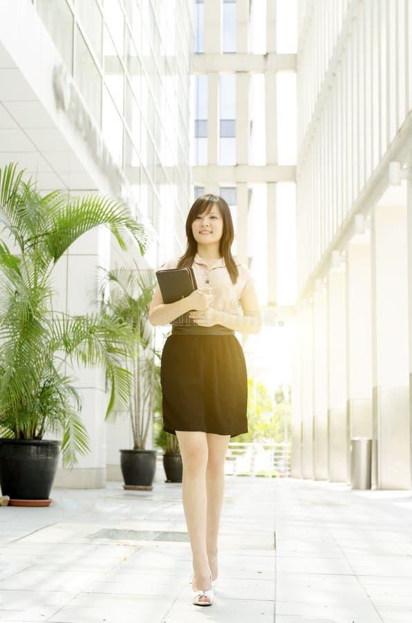 Giovane camminata asiatica del dirigente di donna fotografia stock