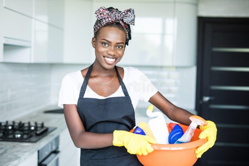 Giovane canestro africano sorridente della tenuta della donna con attrezzature per la pulizia a hause fotografia stock libera da diritti