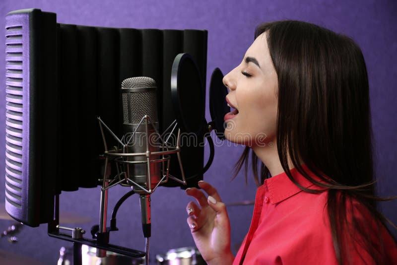 Giovane cantante con la canzone della registrazione del microfono fotografia stock