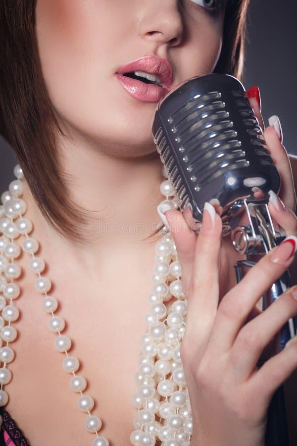 Giovane cantante con un retro microfono fotografia stock libera da diritti