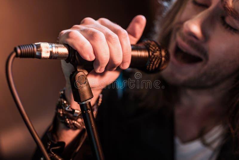 Giovane cantante maschio con il microfono in scena fotografia stock libera da diritti