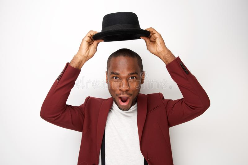 Giovane cappello felice della tenuta dell'uomo di colore sopra la sua testa fotografie stock libere da diritti