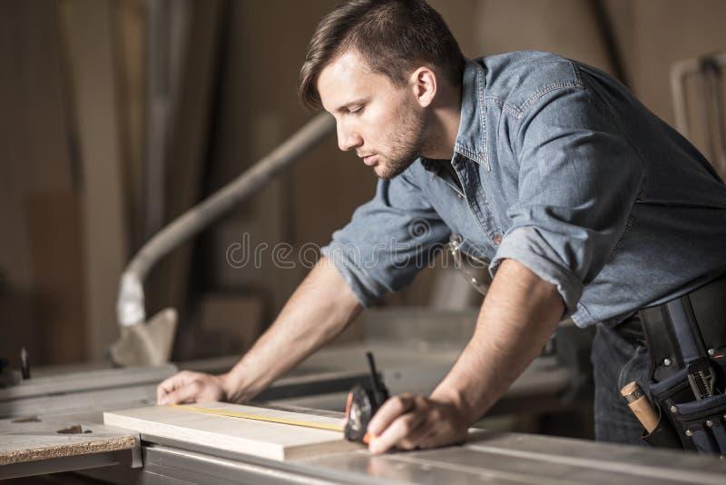 Giovane carpentiere che per mezzo del nastro di misurazione fotografie stock libere da diritti