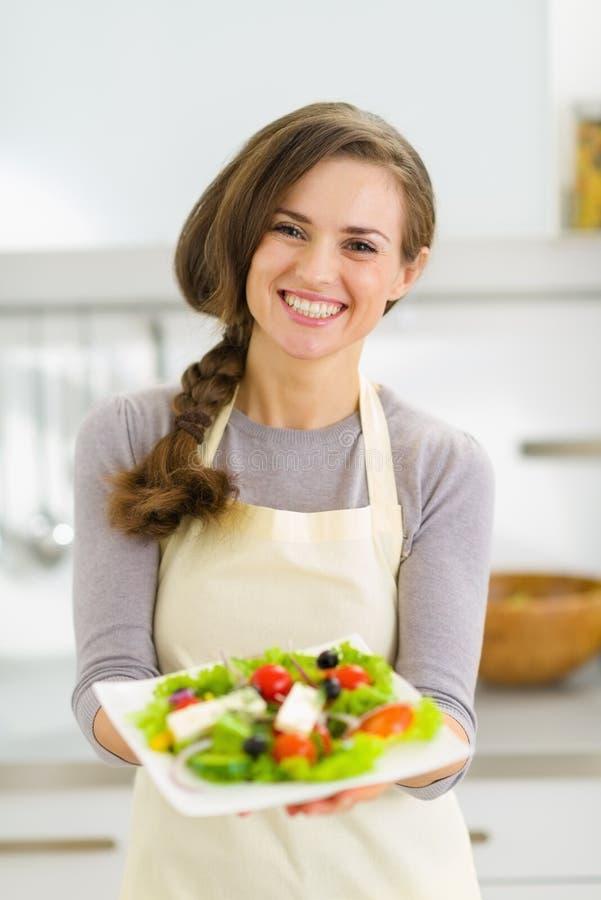 Giovane casalinga felice che dà insalata fresca immagine stock libera da diritti