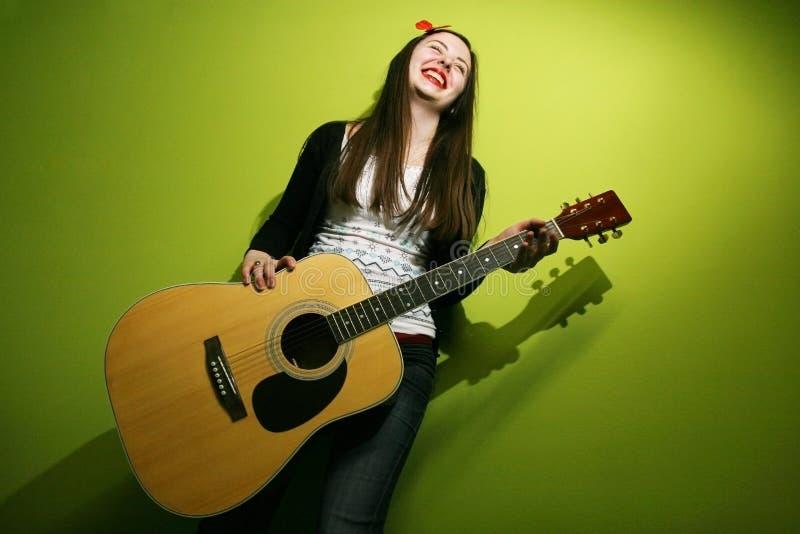 Giovane castana gode della chitarra di gioco fotografia stock libera da diritti