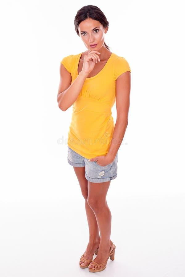 Giovane castana premuroso toccando il suo mento fotografia stock