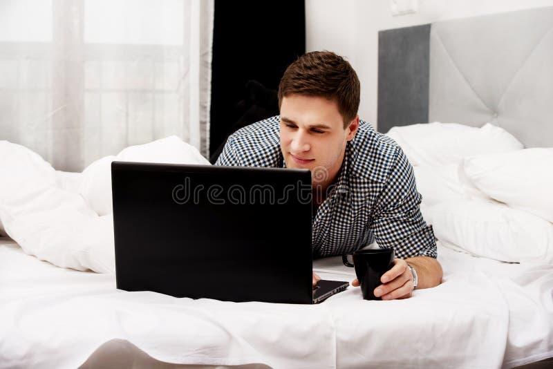 Giovane casuale che per mezzo del computer portatile a letto a casa immagini stock libere da diritti