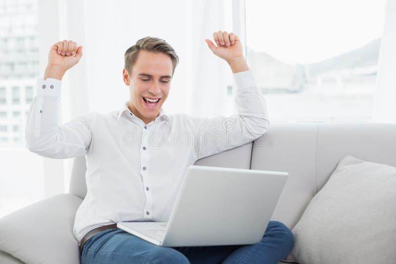 Giovane casuale che per mezzo del computer portatile mentre incitando sofà fotografia stock