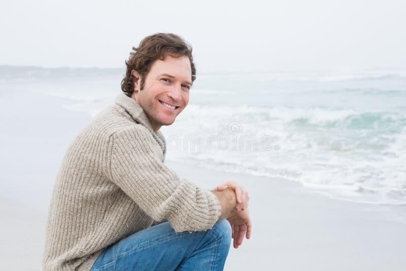Giovane casuale sorridente che si rilassa alla spiaggia immagine stock