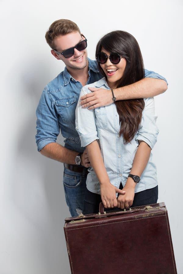 Giovane caucasian che sorride mentre dando alla sua amica asiatica una parte posteriore fotografia stock libera da diritti