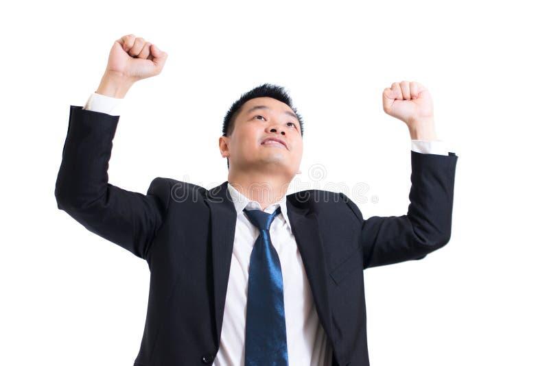 Giovane celebrazione asiatica dell'uomo d'affari riuscita Uomo d'affari felice e sorriso con le armi su mentre stando sul fondo b immagini stock libere da diritti