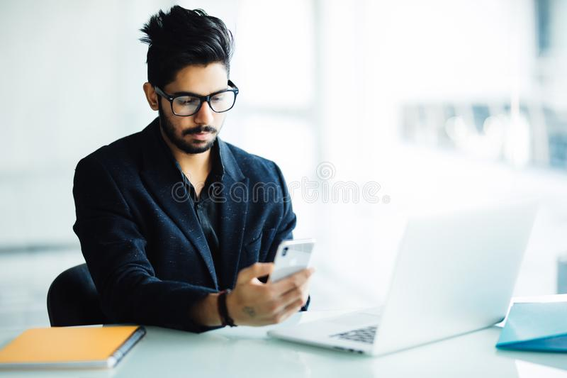 Giovane CEO indiano della società nel suo ufficio di affari allo scrittorio, leggente testo sullo smartphone immagini stock libere da diritti