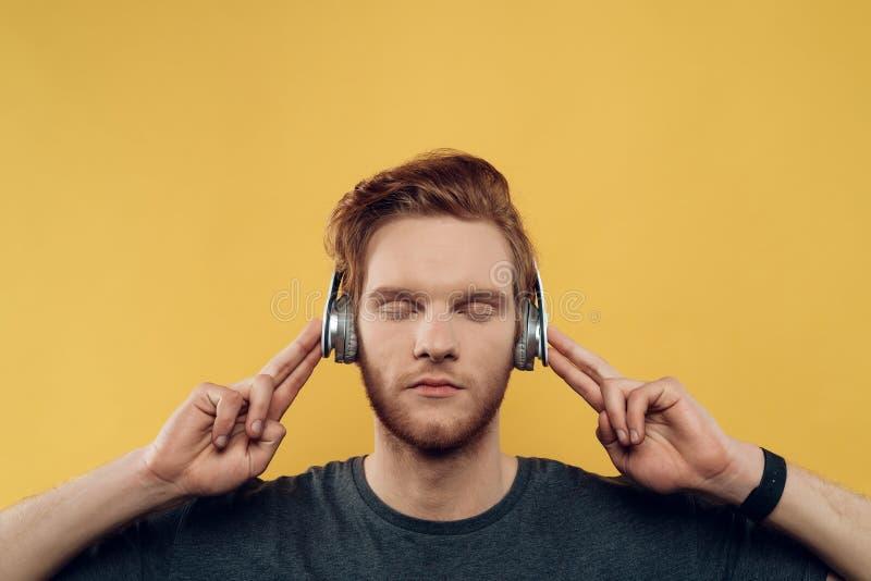 Giovane che ascolta la musica con le cuffie fotografia stock libera da diritti