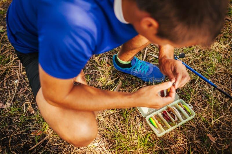 Giovane che attacca esca al gancio di filatura Attrezzatura di pesca L'uomo sceglie il richiamo in scatola ingranaggi di attrezza fotografie stock