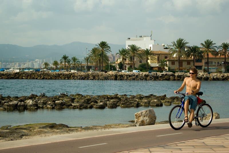 Giovane che biking lungo il mare immagine stock