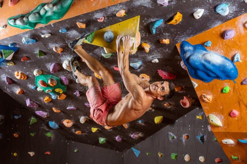 Giovane che bouldering nella palestra rampicante dell'interno, risolvente sfidare fotografia stock