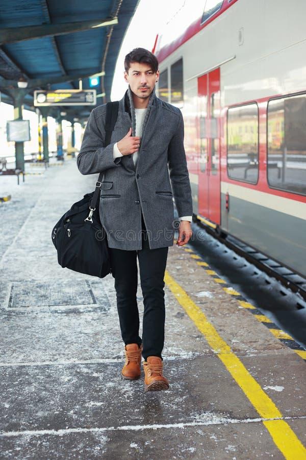 Giovane che cammina alla stazione ferroviaria immagine stock