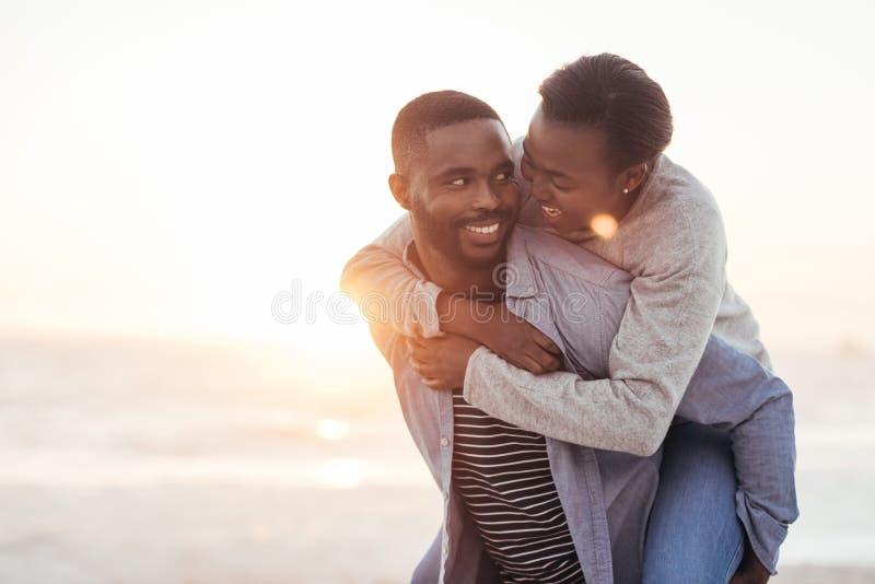 Giovane che dà alla sua amica un a due vie alla spiaggia fotografia stock libera da diritti