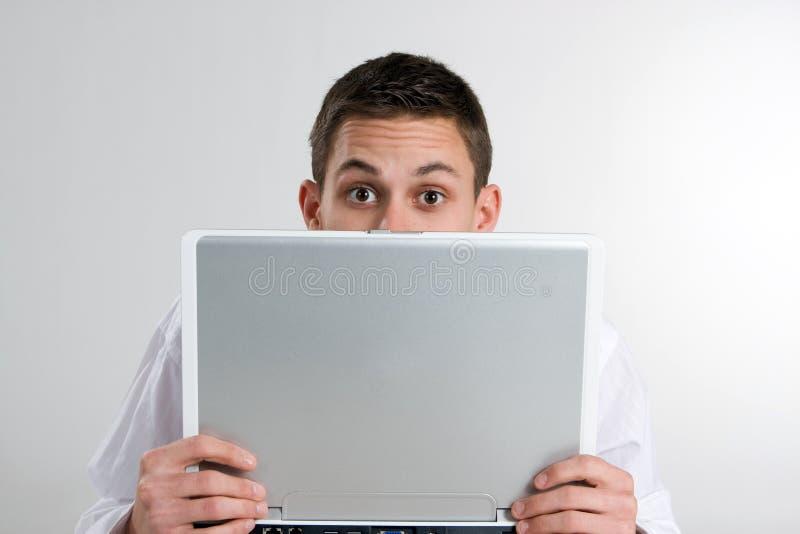 Giovane che dà una occhiata sopra il computer portatile immagine stock libera da diritti