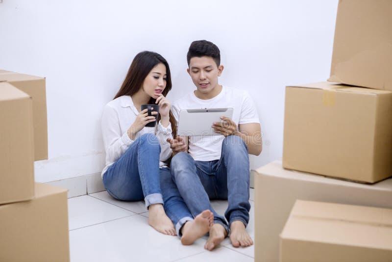 Giovane che dipende dalla sua moglie in una nuova casa immagini stock
