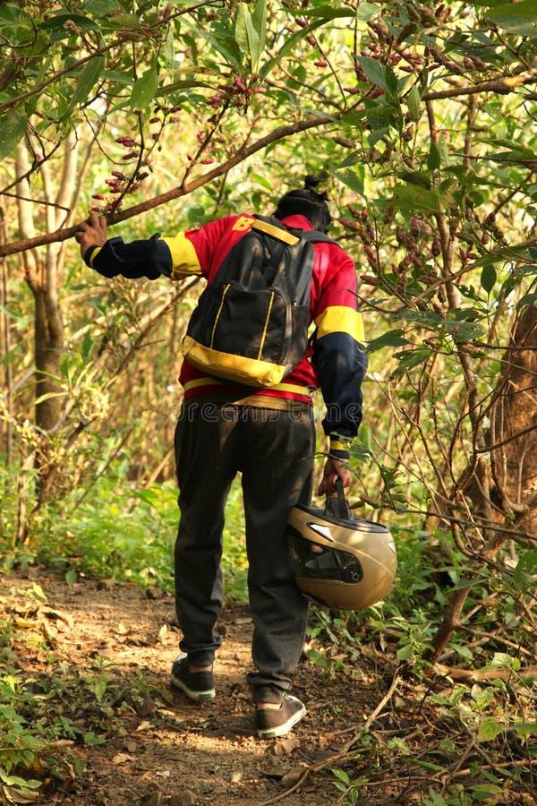 Giovane che fa un'escursione nella giungla tropicale con lo zaino Viandante maschio con lo Zaino che cammina lungo la pista della immagini stock libere da diritti