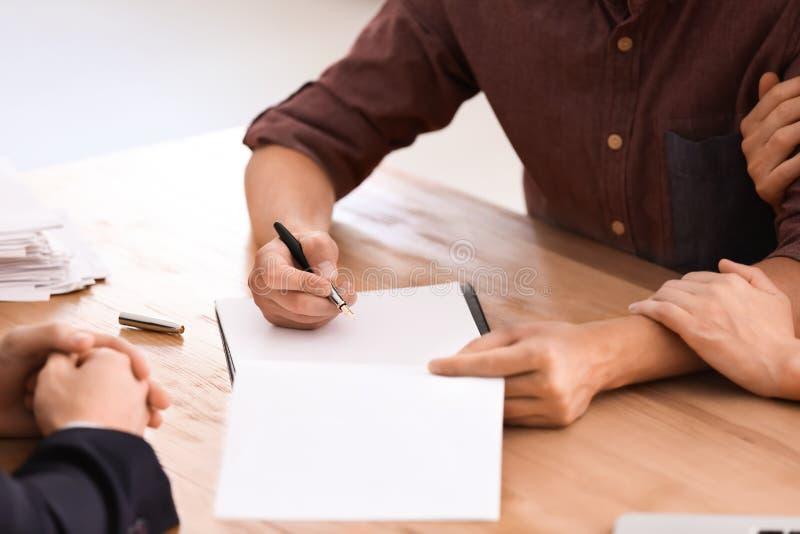 Giovane che firma un contratto per la casa d'acquisto in ufficio dell'agente immobiliare fotografia stock