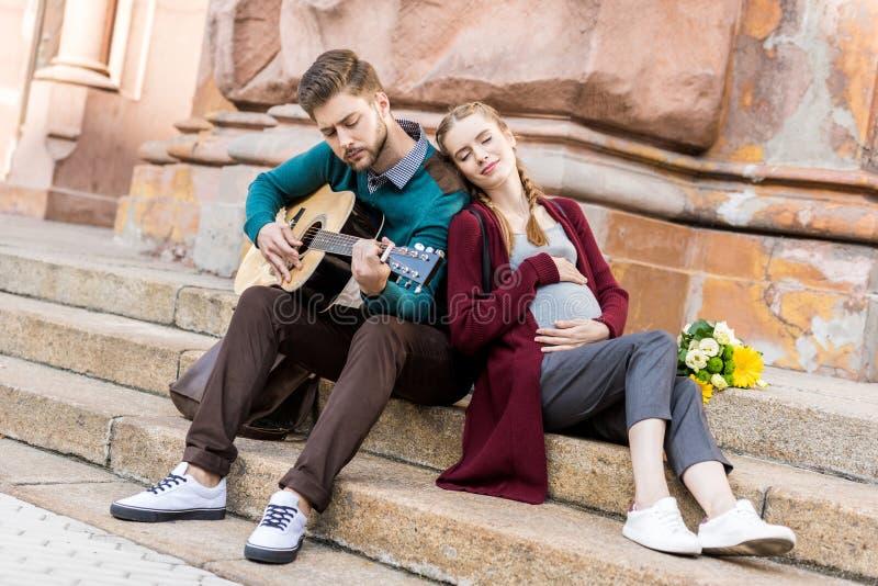 giovane che gioca chitarra per la moglie incinta mentre riposando fotografia stock