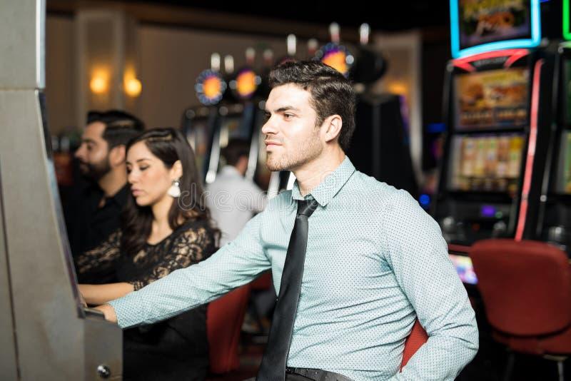 Giovane che gioca in slot machine fotografia stock libera da diritti