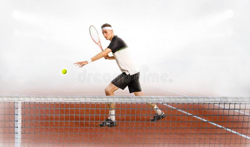 Giovane che gioca a tennis sulla corte fotografie stock