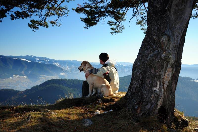 Giovane che gode del Mountain View con il suo cane fotografia stock libera da diritti