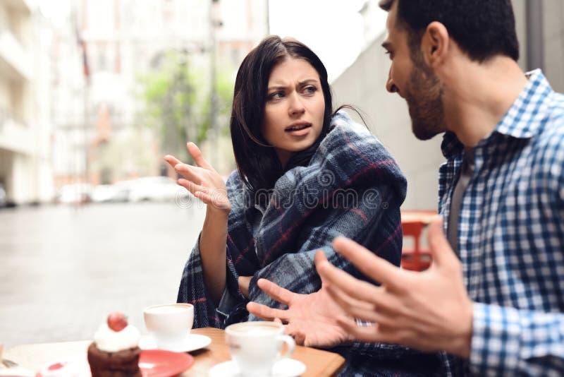 Giovane che grida alla ragazza alla tavola in caffè fotografie stock libere da diritti
