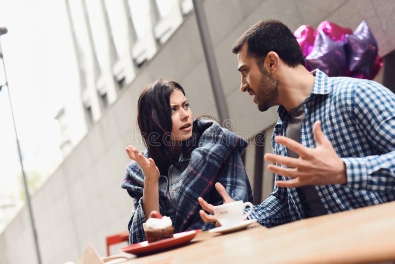 Giovane che grida alla ragazza alla tavola in caffè fotografia stock libera da diritti