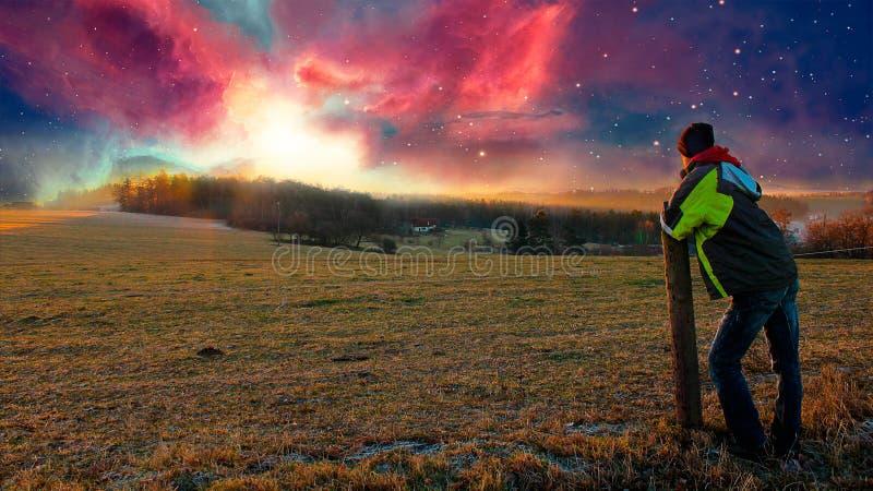 Giovane che guarda al tramonto della nebulosa, manipolazione della foto fotografia stock libera da diritti