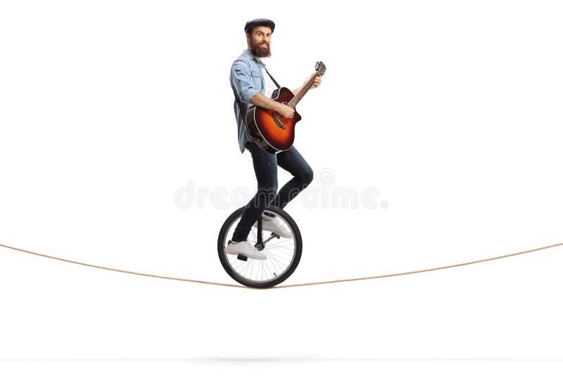 Giovane che guida un monociclo su una corda e che gioca una chitarra acustica fotografia stock libera da diritti
