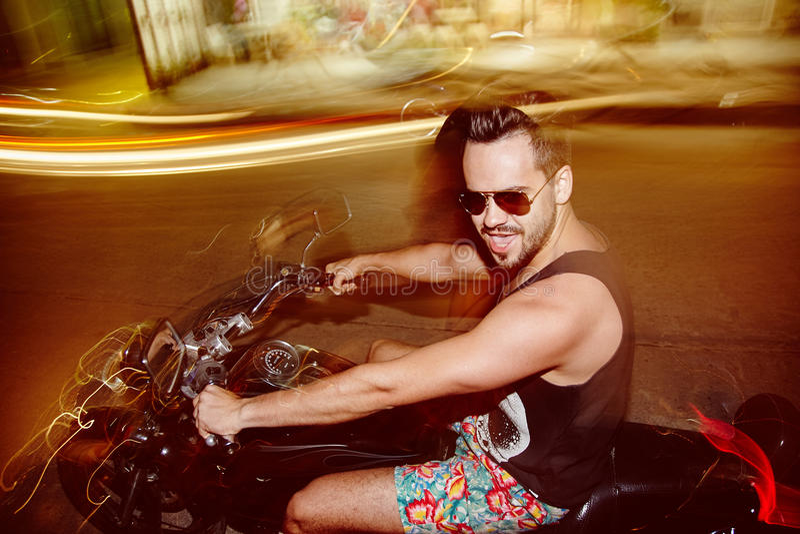 Giovane che guida un motociclo nella notte senza casco immagini stock