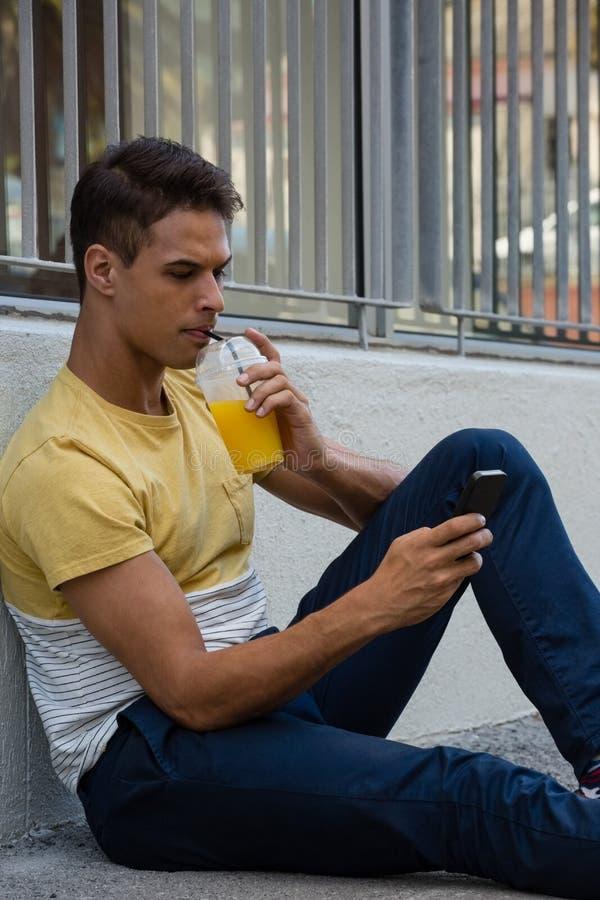 Giovane che ha bevanda mentre per mezzo del telefono cellulare immagine stock